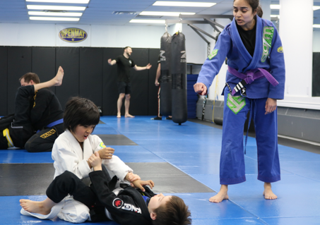 2 kids performing martial arts with insstructor helping