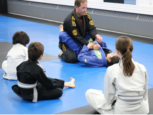 kids martial arts instructor demonstrating move from closed guard