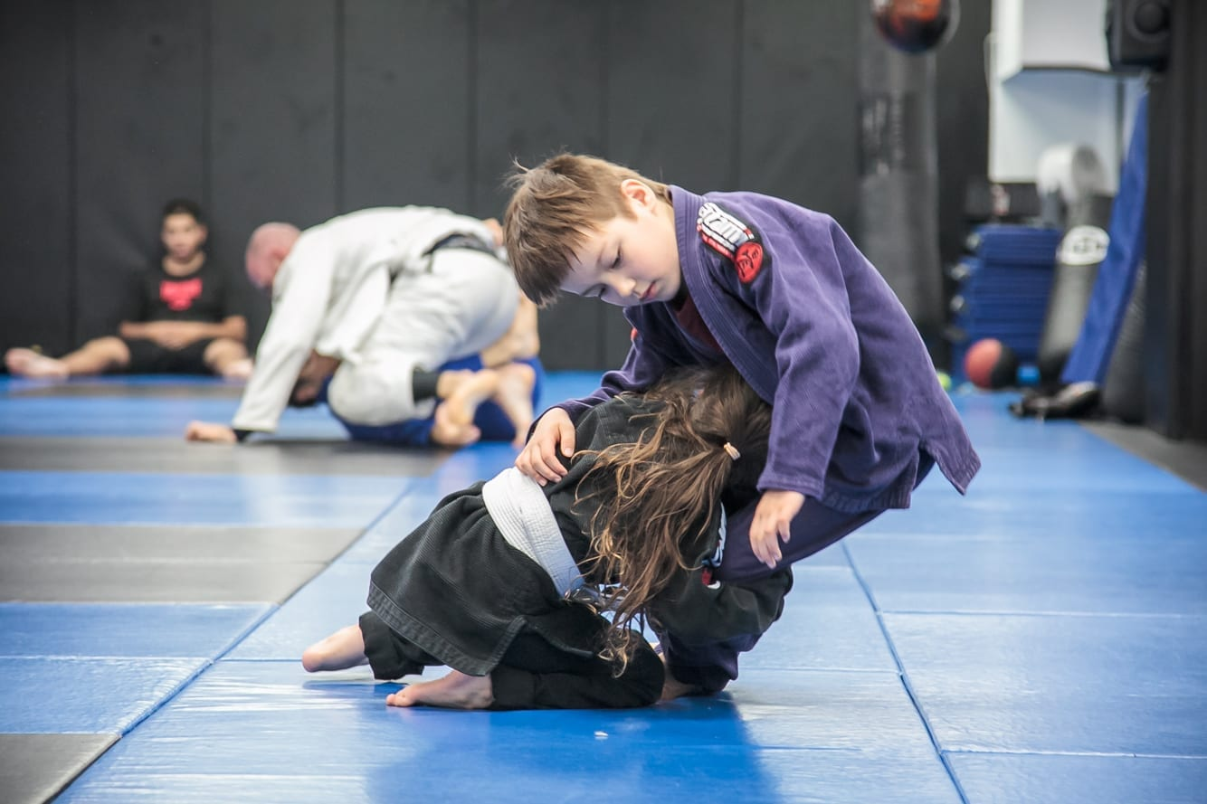 2 kids performing martial arts with big smiles