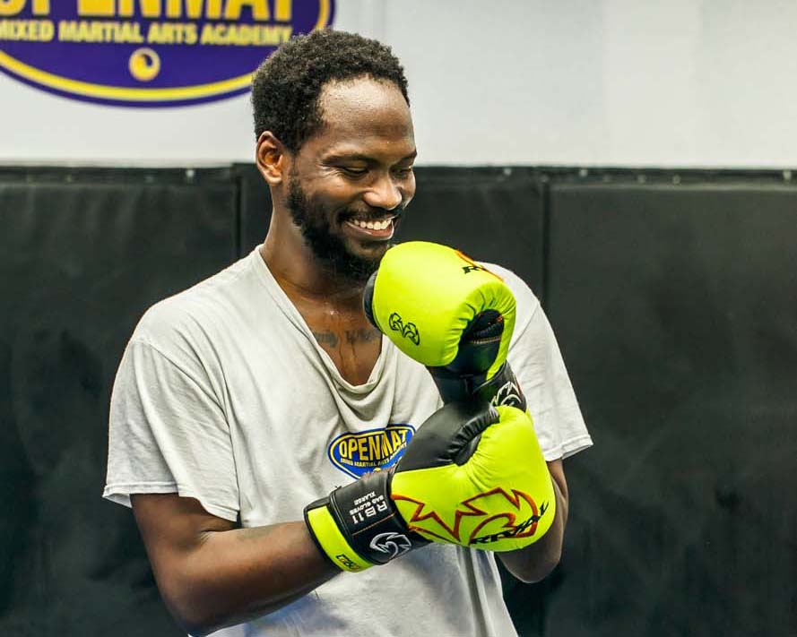 Muay Thai Instructor wearing boxing gloves and smiling