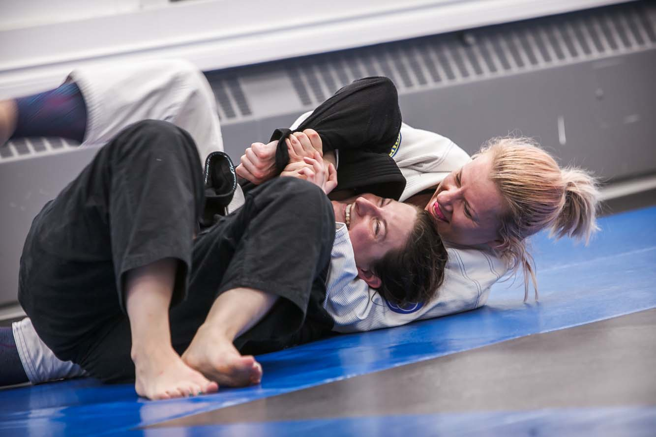 Two women smiling while doing BJJ