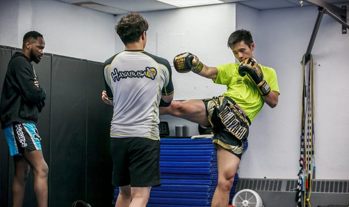 Man kicking Muay Thai pads while coach watches