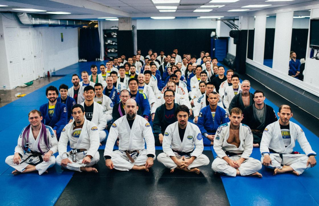 Group photo of OpenMat MMA sitting in rows on the mats after a BJJ Belt test